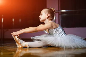 A little adorable young ballerina in white dress sitting on woody floor and dance studio background. Beautiful baby girl dreaming to become professional ballet dancer, classical dance school