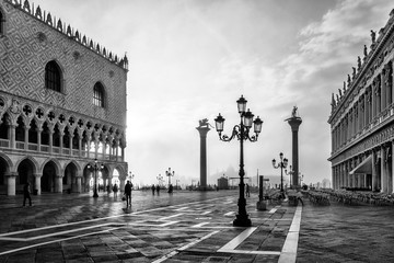 Black and white photo of San Marco square in Venice at sunrise with Doge's Palace, Palazzo Ducale and Saint Mark Column