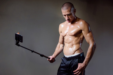 The athlete takes pictures of himself. Man with muscles. Inflated man. Bodybuilder A man photographs the muscles. Athlete.