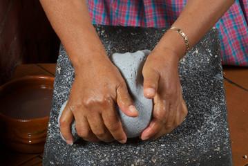 mujer amasando en metate masa de maìz azul para hacer tortillas