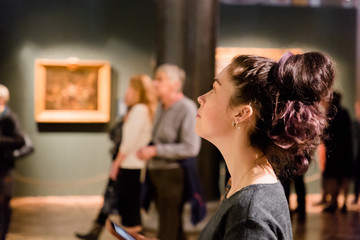 Young women waching arts at the museum. Excursion with group Fototapete