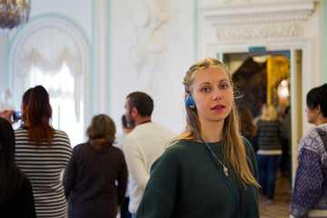 Portrait of girl with light hair listening audioguide in tourist group. White wall of museum on the background