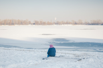 The theme is old age, loneliness and retirement age. Social theme. An old man woman sits with his back and looks at the frozen lake and thinks. Death death and end of life