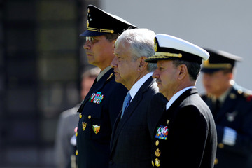 Mexico's new President Andres Manuel Lopez Obrador, flanked by Secretary of Defense Luis Sandoval and Secretary of the Navy Admiral Rafael Ojeda Duran, are seen after reviewing troops at Campo Marte in Mexico City