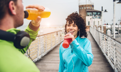 Man and woman drinking energy drink from bottle after fitness sport exercise