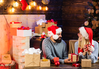 Merry Christmas and Happy New Year. Portrait of a young beautiful smiling couple. Winter holidays and people concept. Sensual couple for Christmas. Hoppy couple over christmas tree lights background.