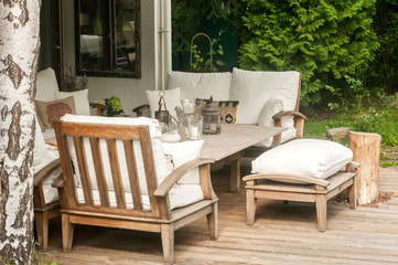 Home garden wooden furniture with table, chairs and cushions on wooden boards floor