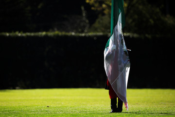 A military cadet is silhouetted while holding a Mexican flag during a troop review by Mexico's new President Andres Manuel Lopez Obrador at Campo Marte in Mexico City