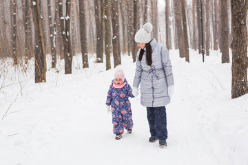 Winter, family and people concept - mother is walking with her daughter in winter forest.