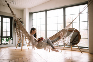 Dark-haired girl dressed in pants, sweater and warm slippers reads a book lying in a hammock in a cozy room with wooden floor and panoramic windows and a round mirror on the floor Fotomurais