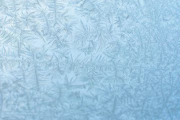 frozen glass with a pattern of frost against a blue sky