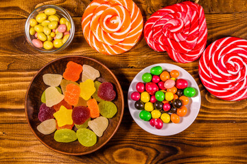 Different sweet candies on a wooden table. Top view