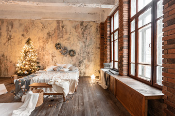 Loft style apartments. Bed in the bedroom, high large Windows. Brick wall with candles and Christmas tree. warm and brown color