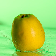 Green apple and splashes of water on a colored background