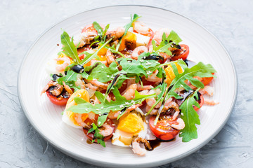 Ready-to-eat salad with cherry tomatoes, eggs, boiled shrimp, arugula, sesame seeds and balsamic sauce in a plate on the table