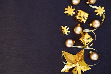 Golden Christmas decoration on black background. Golden Xmas. Flat lay. Merry Christmas and Happy New Year