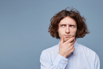 Confident pensive handsome young man doubts, touching face while thinking is looking away wearing white shirt, standing on the blue background. Empty copy space for promotion Wall mural