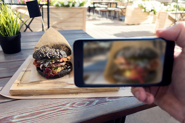 Food photography of tasty black burger in outdoors cafe. Man hands taking food photo by mobile phone