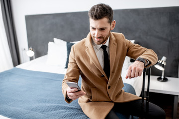 Dressed businessman sitting on the bed with a suitcase using phone before departure from the hotel room