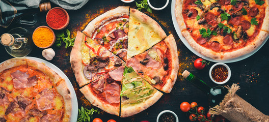 Foto op Canvas Pizzeria A set of Italian pizza. Italian cuisine. On a black wooden background. Free copy space. Top view.