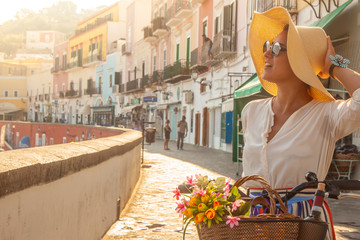 Young woman with bike at Ponza Island harbor pier in Italy. Tourist with large hat, fashion shirt and colorful skirt. Basket with wine and flowers in front of shops and boats.
