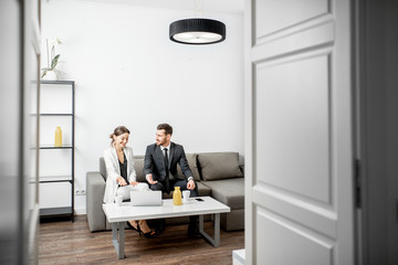 Elegant businessman and woman sitting together on the couch during the work with laptop at home or comfortable office. Wide view with copy space