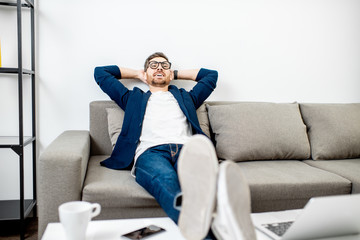 Businessman dressed casually relaxing on the couch while watching TV at home