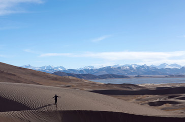 An unidentified tourist over sand dunes in Western Tibet, China