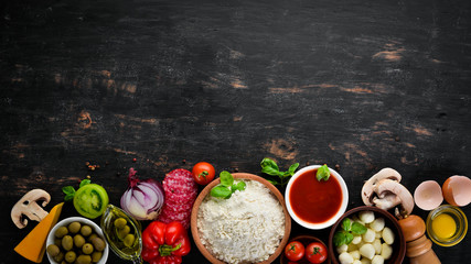 Ingredients for pizza. Mushrooms, sausages, tomatoes, vegetables. Top view. On a black wooden background. Free copy space. Wall mural