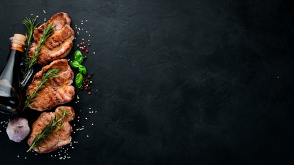 Meat steaks with rosemary. Grill, barbecue. On a black stone background. Top view. Free copy space.