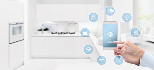 smart home automation control concept hand touch cell phone screen with blue symbols icons on kitchen background web banner and copy space template