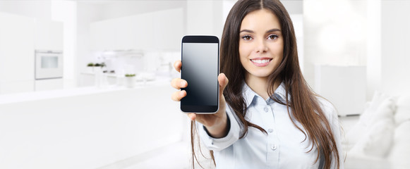 smart home control concept smiling woman showing cell phone screen on kitchen and living blurred background
