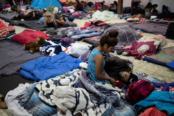 Migrants, part of a caravan of thousands from Central America trying to reach the United States, rest in a temporary shelter in Tijuana