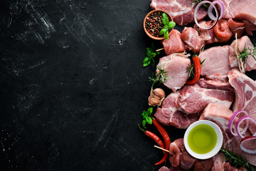 Raw meat for barbecue. Meat with spices and herbs. On a black stone background. Top view. Free copy space. Wall mural