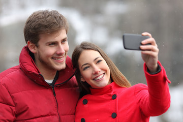 Happy couple taking selfies in winter holiday