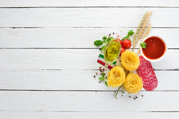 Dry pasta. Pasta and fresh vegetables. Top view. On a white wooden background. Free copy space.