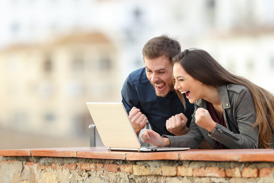 Excited couple reading online good news on laptop