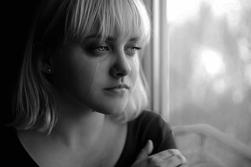 Close up of crying depressed young blond woman near window at home. Sadness, nostlagic, depression. Black and white photo.