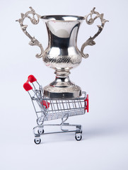 shopping  cart and silver cup on white background