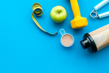 nutrition for workout with protein cocktail and bars on blue background top view mockup