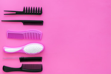 Set of professional hairdresser tools with combs pink background top view mockup