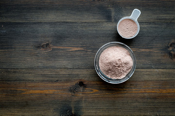 sport nutrition set with protein powder for cocktail and scoop on wooden background top view space for text