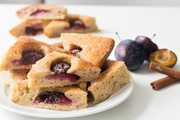Triangle shaped plum cake served on plate. Fresh fruit and cinnamon in the background.