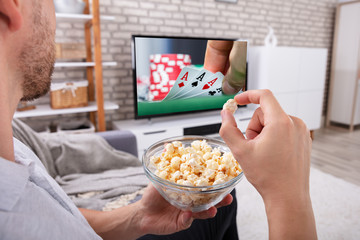Man Eating Popcorn While Watching Television