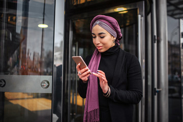 Young arabian woman stands at glass door and hold phone in hands. She points on it. Young woman smiles.