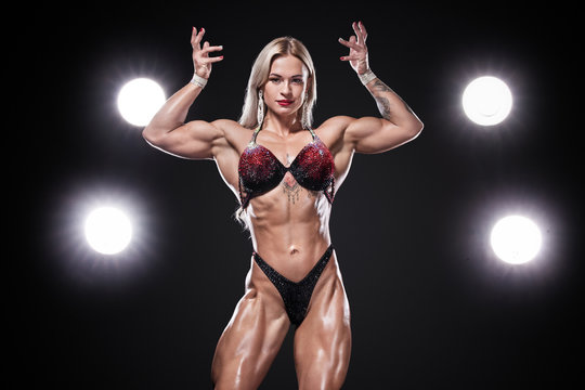Bodybuilding competitions on the scene. Women sportsmen and athlete. Black background with lights.