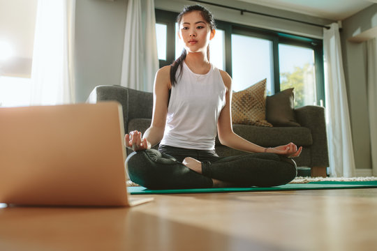 Girl looking at laptop and doing yoga at home