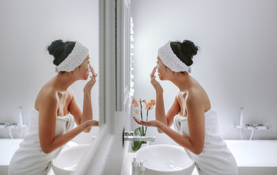 Woman in bathroom applying cosmetic on her face