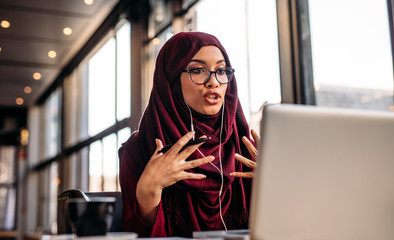 Businesswoman in hijab having a video chat on laptop
