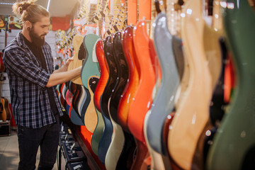 Young hipster with long hair up stand in front of electic guitars andtouch them. He choose. Man in alone in room. Many colorful guitar bodies are on picture.